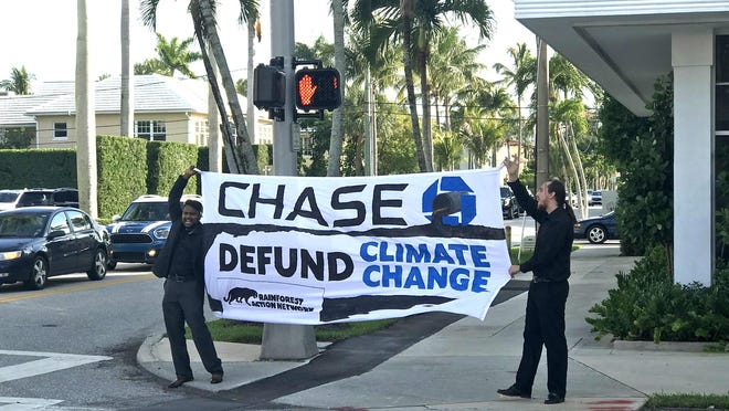 """Protesting on behalf of Rainforest Action Network, Mathi Mugilan of Palm Beach County and Nil Lian of Broward County hold a sign with the words """"Chase"""" and """"Defund Climate Change"""" Wednesday at the corner of Royal Palm Way and Cocoanut Row in Palm Beach."""