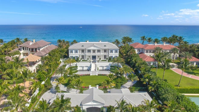 At 640 S. Ocean Blvd. in Manalapan, a porche-cochere with a guesthouse and staff quarters can be seen in the foreground. Driveways pass through formal gardens and lead up to the front door.