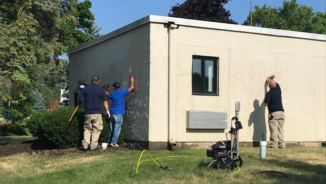 Workers remove hateful graffiti spray-painted on the rental office of the Pines of Perinton on July 2.