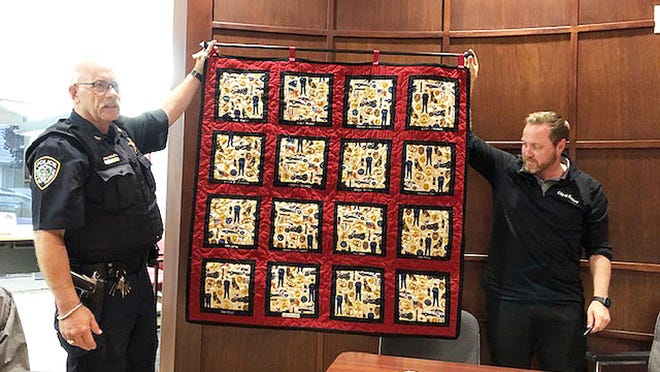 Chief Robert McCormick, left, and City Superintendent Brett Ashburn display a quilt made by Margie Hedrick at Wednesday's Fairbury City Council meeting.