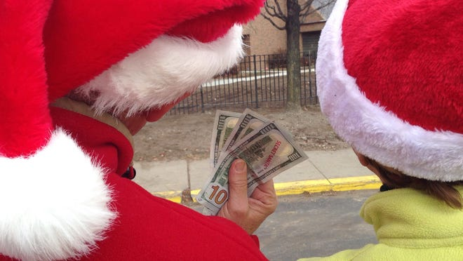 Elf No. 32A, left, and Mrs. Claus show some of the cash they brought to hand out to strangers in Detroit and Lincoln Park on Friday.