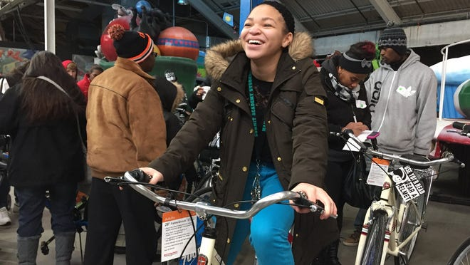 Sakiya Harris, 14, of Taylor shows off the new Schwinn bicycle she chose at the Toys for Tots event in Detroit on Saturday.
