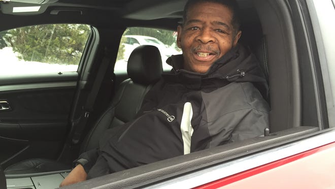 James Robertson, 56, of Detroit sits Sunday, Feb. 8, 2015, in his new Ford Taurus, a gift from a Sterling Heights dealer.