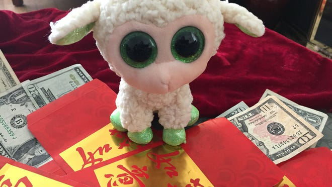 It's a tradition to give red envelopes with cash to children and unmarried relatives for the Chinese New Year. The money symbolizes the wish for good fortune for the next generation. This is the Year of the Sheep.