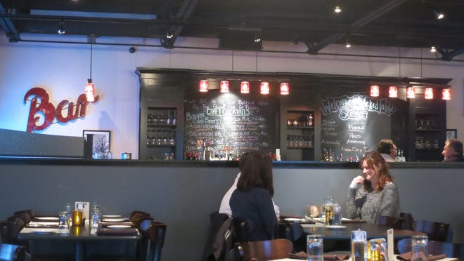 A long, softly lit bar is separated from the dining room by a low wall at the Wicked Table restaurant in Farmington Hills.