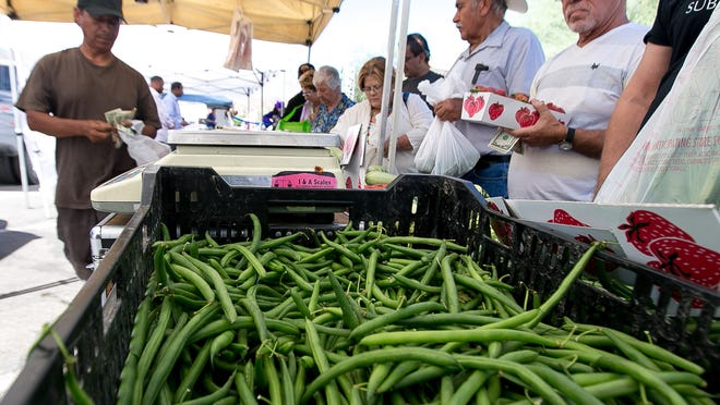 Vendor Antonio Buenrostro (left) of Riverside helps customers during the Cathedral City Farmers Market held at Cathedral City Civic Center on Sunday morning.