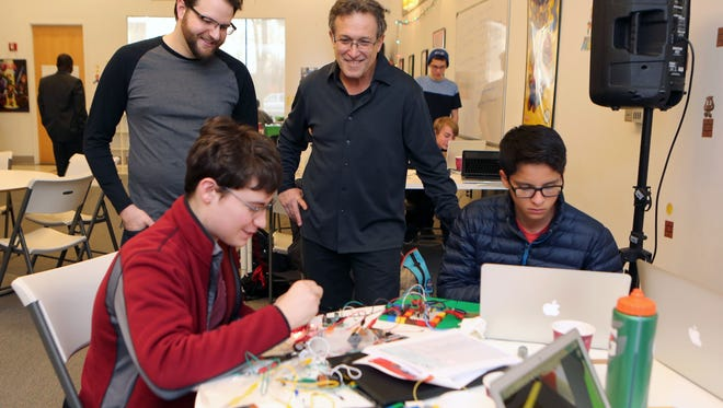 Rob Kissner, president of the Digital Arts Experience and Alan Brody look on as Mamaroneck High School team members Andrew Katz and Pablo Garza work on a railroad crossing design contest at the Digital Arts Experience in White Plains, Dec. 3, 2016. The event was sponsored by Alan Brody, whose wife was killed at Metro-North train crossing in Valhalla.  Not pictured were teammates Paul Pedroso and Samuel Brause.