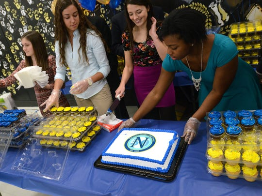 Members of the Student Council prepare a cake during the 50th birthday celebration Monday, Jan 26, at Port Huron Northern.