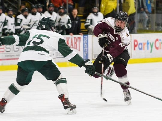 Lyndon's Krystof Vanek (24) shoots the puck past Woodstock's Charles Greene (15) during the Vermont state division II boys hockey championship game between Lyndon and Woodstock at Gutterson Field House on Monday evening March 19, 2018 in Burlington.