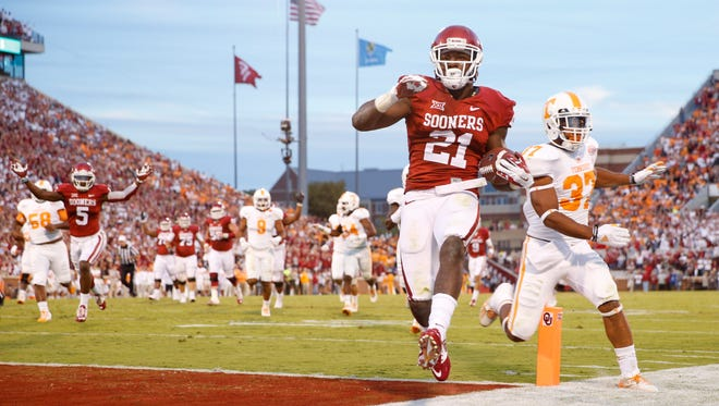 Oklahoma's Keith Ford (21) runs for a first-quarter touchdown past Tennessee  defensive back Brian Randolph (37) on Saturday in Norman, Okla.