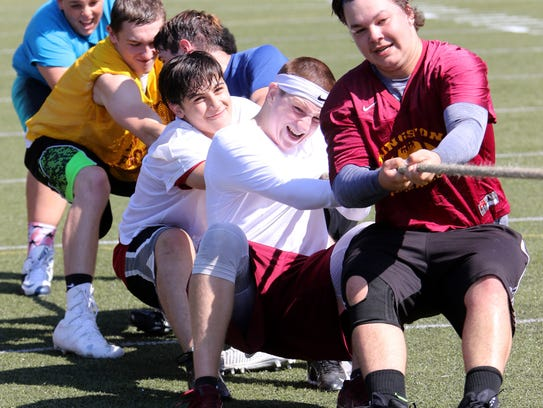 Members of Kingston's football team engage in a tug-of-war