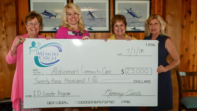 Martin County Memory Circle founders Ann Young, left, and Doris Clements, right, present a check for $23,000 to Alzheimer's Community Care representatives Amy Bromhead and Mary Barnes.