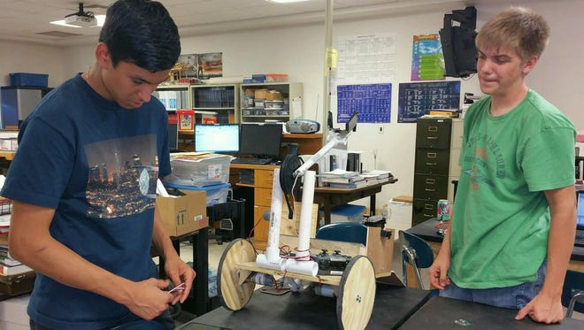 MESA President Beda Prieto and MESA Technical Manager Jacob Brown work to rewire Tiger Tech's robot. Tiger Tech took third place overall in the statewide competition and will compete in regional in December.