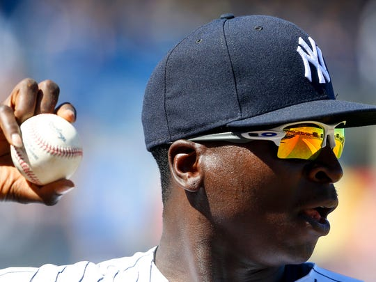 Yankees shortstop Didi Gregorius (18) looks to throw the ball to a teammate as they walk off the field in the fourth inning of a baseball game against the Philadelphia Phillies during spring training at George M. Steinbrenner Field on Friday, Feb. 24, 2017.