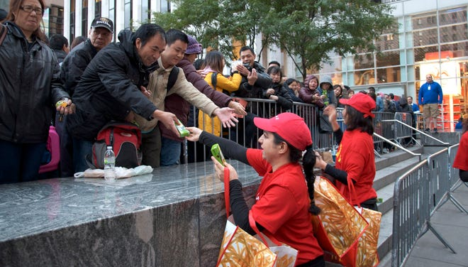McDonald's workers hand out apple pies and apple slices to those waiting in line for the new iPhone 6 in New York.