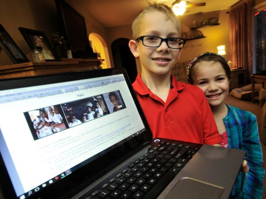 Trevor Holden and his sister, share an adoption website they have been viewing with their parents recently in Guilford Township. Their parents, Patrick and Karen Holden are planning to adopt a child from Haiti.