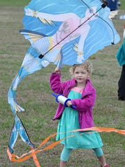 Violet Howard, 3, of  Seaford works to get her kite airborne at the 48th Great Delaware Kite Festival on Friday.