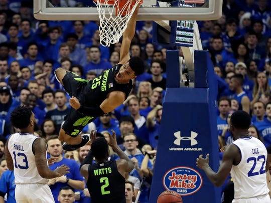 Michigan State forward Malik Hall (25) hangs from the rim after a slam dunk in front of Seton Hall guard Myles Powell (13) during the second half of an NCAA college basketball game Thursday, Nov. 14, 2019, in Newark, N.J. (AP Photo/Adam Hunger)