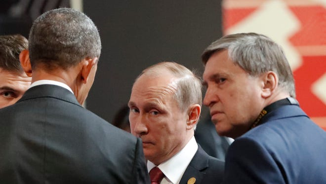President Obama talks with Russian President Vladimir Putin and Kremlin foreign affairs adviser Yuri Ushakov at the opening session of the Asia-Pacific Economic Cooperation (APEC) in Lima, Peru, Sunday.