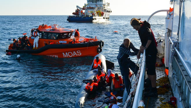 Rescuers pull refugees from the Mediterranean Sea after their rubber boat capsized roughly 20 miles off the coast of Libya on Nov. 22.