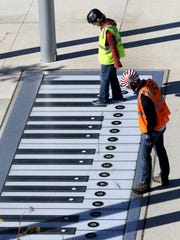 People try out the giant foot piano at Smale Riverfront