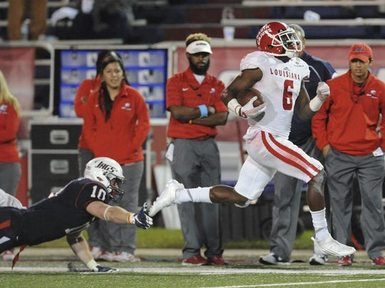Ragin' Cajuns defensive back Savion Brown (6) breaks the tackle of South Alabama Jaguars linebacker Tavon Cox (10) on a pick six during their NCAA football game at Ladd-Peebles Stadium Thursday in Mobile, Ala.