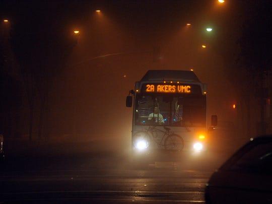 A Visalia City bus makes its way down Center Ave. as the fog rolls into downtown Visalia Monday evening.