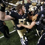New Orleans Saints kicker Kai Forbath is mobbed by teammates after kicking the game winning field goal at the end of regulation in the second half of an NFL football game against the New York Giants on Nov. 1 in New Orleans. The Saints won 52-49.
