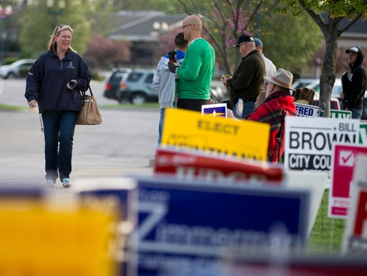 Jennifer Atkinson heads to a polling spot as she is courted by campaigners for a variety of candidates in Fishers, Tuesday, May 6, 2014. Among other races, a first-ever Fishers mayoral primary is being held.