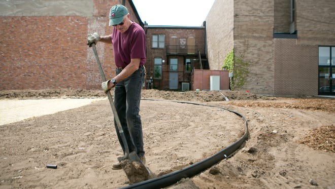 Tom Girolamo of Eco-Building & Forestry begins work on the sustainable garden outside of Great Lakes Higher Education Corp. in downtown Stevens Point on Thursday.