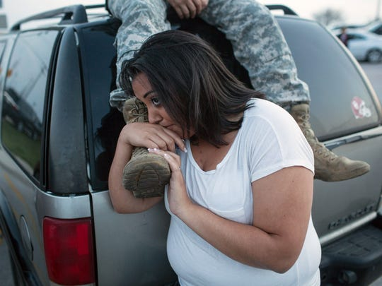 In this April 2, 2014 file photo, Lucy Hamlin and her husband, Spc. Timothy Hamlin, wait for permission to re-enter the Fort Hood military base, where they live, following a shooting on the base, in Fort Hood, Texas.