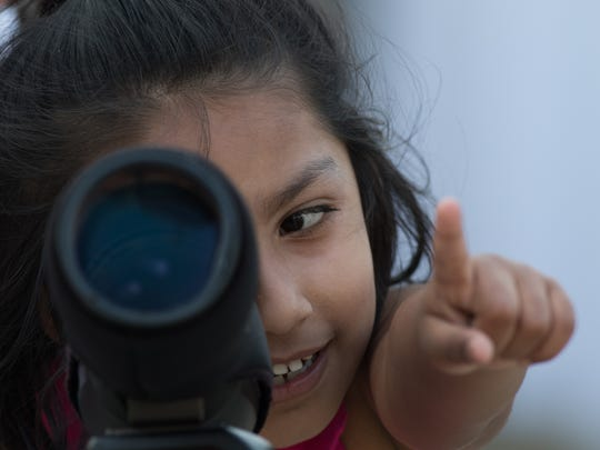 Rayya Karim, 6, observes peregrine falcons during the 8th annual Falcon Watch put on by the Delaware Ornithological Society in Wilmington Wednesday.