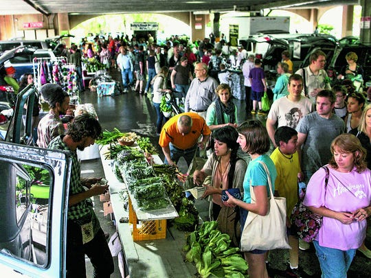 Customers and vendors are seen at the season's first farmers market at the Chauncey Swan Parking Ramp on Wednesday, May 2, 2012.