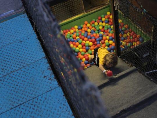 Lincoln Bopp, 3, of Coralville, runs through an amusement park ride at the Johnson County Fair on Friday, July 28, 2012.