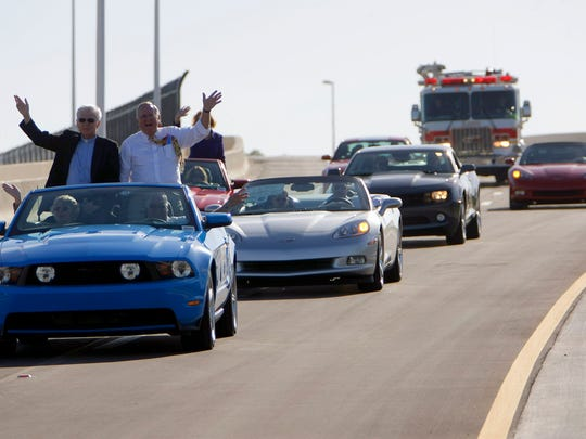 In this file photo, Rev. Hugh McGuigan, left, and Lee County Commissioner Frank Mann, right, wave to a crowd at the base of the new Estero Parkway extension bridge Friday as they drive across it for the first time. The dedication and ribbon cutting ceremony for the Estero Parkway Extension project took place Friday morning at the bridge's base with numerous Lee County officials on hand as well as members of the public. The project took two years and provides access over Interstate 75 from Ben Hill Griffin Parkway to Three Oaks Parkway and onto U.S. 41.