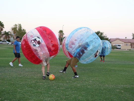 Desert Bubble Soccer players bump into each other while playing a game at the Thousand Palms Community Park in Thousand Palms on Sunday, August 28, 2016.