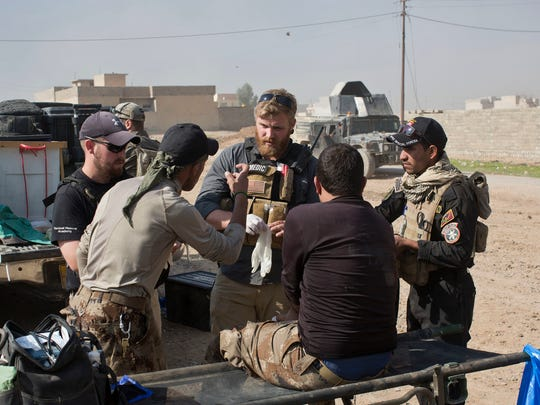 In this Sunday, Nov. 6, 2016 photo, Pete Reed, center, talks to Iraqi special forces soldiers at a field clinic in Gogjali, on the eastern outskirts of Mosul, Iraq. As Iraqi forces struggle to secure recent gains against the Islamic State group in Mosul, casualties are spiking. Iraqi officers say they expect the toll among both civilians and troops to rise as the troops continue to push into the IS-held city center. At the field hospital on Mosul's eastern outskirts, teams of Iraqi and Western volunteer medics are treating a family badly burned by a car bomb, children maimed by booby-trapped explosives and soldiers suffering from shrapnel and gunshot wounds.