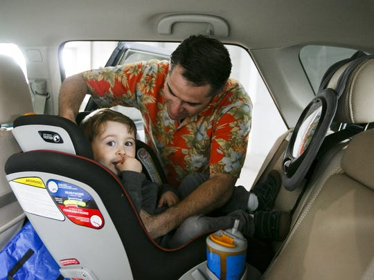 Chris Castelli puts his son William, 2, into a car seat after picking him up from the Family YMCA of Marion & Polk Counties on Friday, May 5, 2017. The YMCA will be closing four early childhood classrooms on June 2.