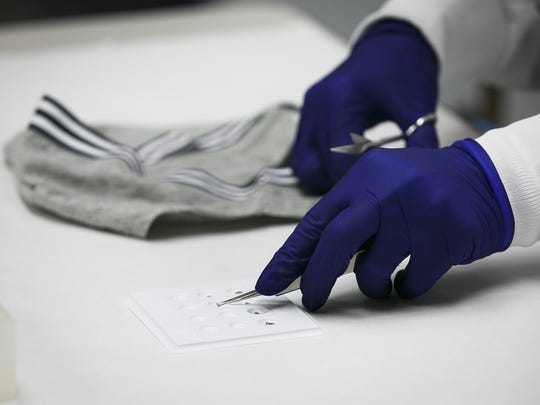 Forensic scientist Jennifer Buttler cuts small pieces of cloth from a sample piece of underwear as she demonstrates the steps required to process a sexual assault forensic evidence kit on Thursday, May 25, 2017, at the Oregon State Police Forensics Services Division. No real evidence was used. No real evidence was used.