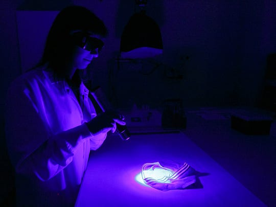 Forensic scientist Jennifer Buttler uses an alternate light source to search for seminal fluid during a demonstration of the steps required to process a sexual assault forensic evidence kit on Thursday, May 25, 2017, at the Oregon State Police Forensics Services Division. No real evidence was used.