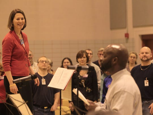 """In this file photo from 2012, Mary Cohen smiles as Arnold Grice greets guests during the """"Look on the Bright Side"""" concert at the Iowa Medical and Classification Center, as known as Oakdale prison."""