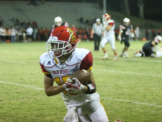 Palm Desert's Simon Gaete gains yards after a catch during the first half of the game against Palm Springs on Friday, October 13, 2017.