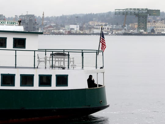 The Puget Sound Naval Shipyard is in the background of the Kitsap Transit passenger ferry Carlisle II from Port Orchard.