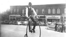 Rene Crombez smiles at the crowd during a Fourth of July parade, balancing on his antique high-wheel bike.