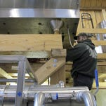 Wendell Downing works on a tank to hold sap to be boiled into maple syrup Wednesday at Limlaw Family Maple Farm in West Topsham, Vermont.