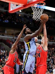 Memphis Grizzlies' JaMychal Green, center, scores between Chicago Bulls' Kris Dunn, left, and Lauri Markkanen, right, during the first half of an NBA basketball game Wednesday, March 7, 2018, in Chicago. (AP Photo/Charles Rex Arbogast)