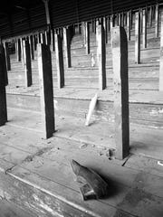 """City workers raze the bleachers at Milwaukee's Borchert Field. The original caption, published in the Dec. 30, 1952, Milwaukee Journal: """"A couple of old bottles, a woman's old shoe and, perhaps, some memories among the tombstone-like uprights of a section of Borchert Field's bleachers are all that are left of the crowds that once filled the now-missing seats."""""""
