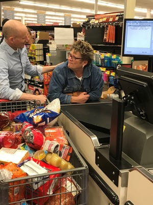 Runner Neil Clifford and Trumansburg Rotary Supermarket Sweepstakes winner Mimi Duncan celebrate their haul at the ShurSave checkout.