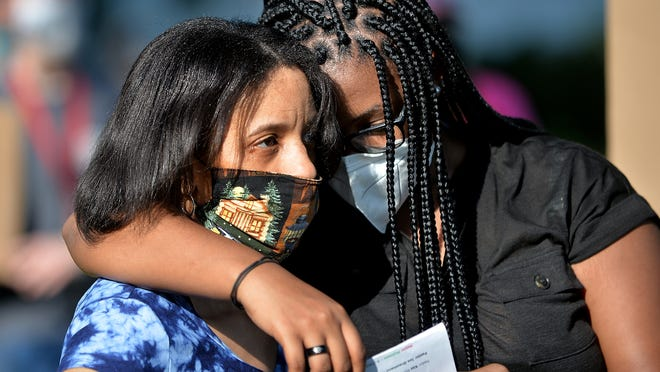 Jasmina Lee, 17, right, of Marlborough, hugs her mother, Antoinette Foster, while listening to speakers during a Juneteenth Celebration Friday on Union Common in Marlborough.