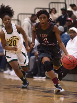 Stanhope Elmore's Jakayla Harris (5) dribbles down the court as Carver's Alayah Johnson (20) chases her during the basketball game on Friday, Feb. 12, 2016, in Montgomery, Ala.